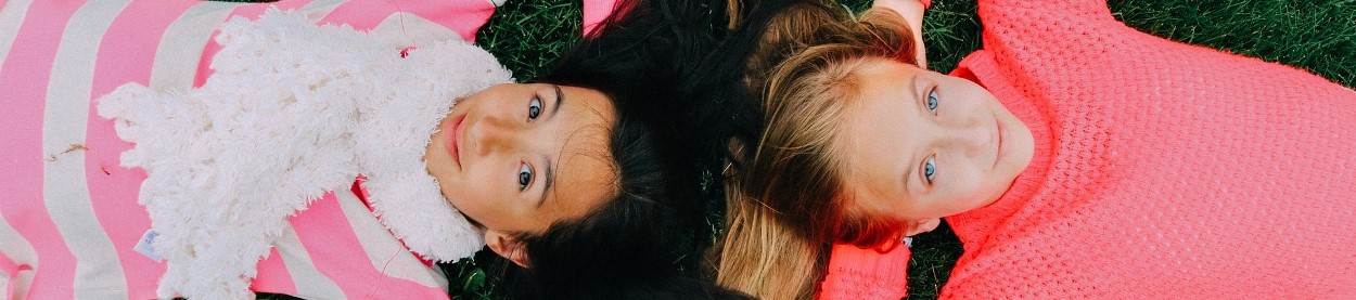 Photo of two girls lying down on a lawn