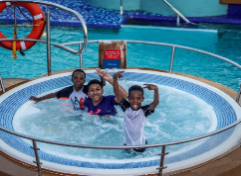 Photo of three boy playing in a swimming pool
