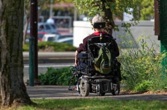 Photo of a person in a wheel chair on the sidewalk