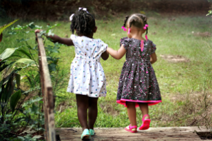 Photo of two small girls walking across a bridge