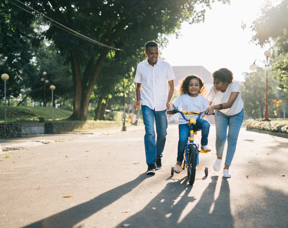 Family with child on a bike taking a stroll