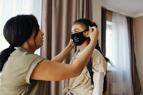 Mother helping daughter put on a face mask